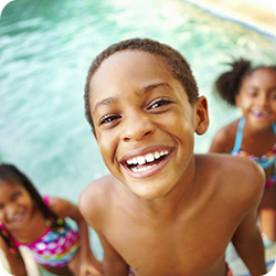 Summer Pool Black Boy with Two Black Girls in Background.jpg